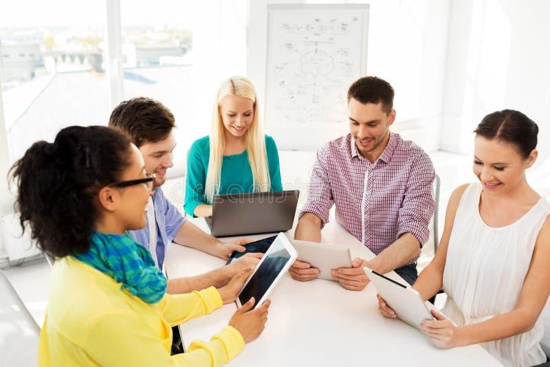 Creatief team met lijstcomputers in bureau stock afbeeldingen