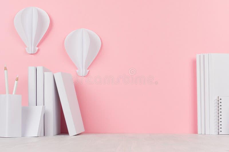 Creatief terug naar schoolachtergrond - witte boeken, kantoorbehoeften en hete luchtballonsorigami op zachte roze achtergrond royalty-vrije stock foto