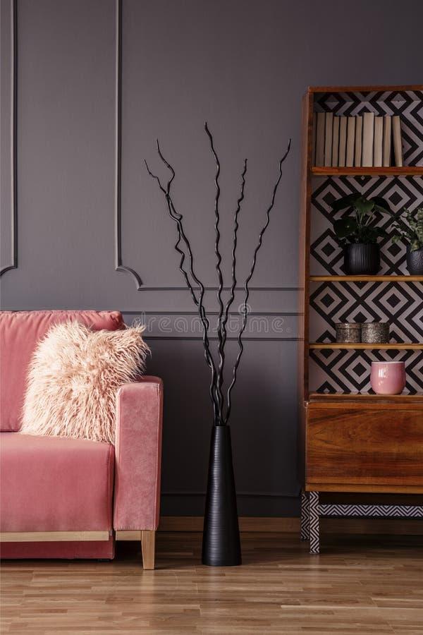 Creatief zwart beeldhouwwerk tussen een comfortabele, roze bank met bont stock foto