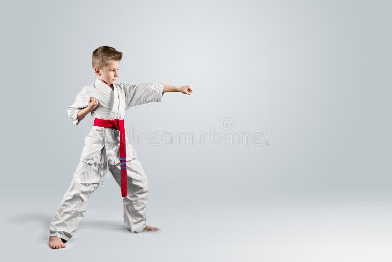 Creatieve achtergrond, baby in witte kimono op een lichte achtergrond Het concept vechtsporten, karate, sporten sindsdien stock afbeelding