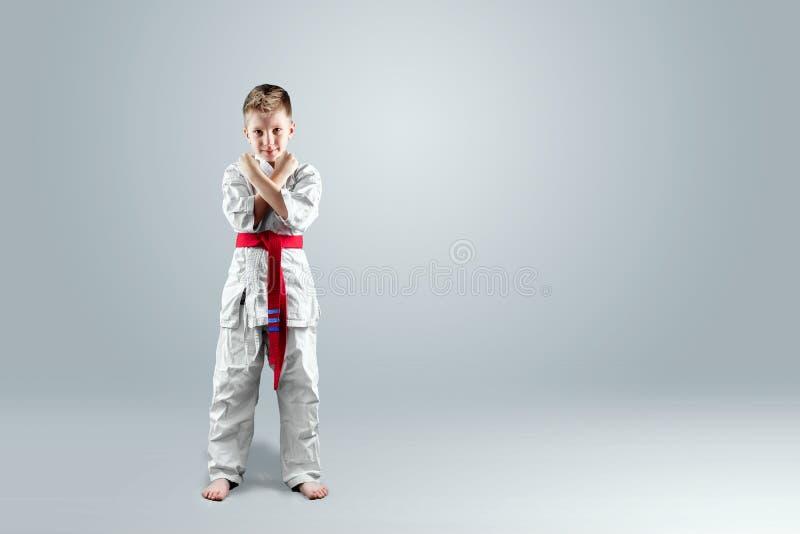 Creatieve achtergrond, een kind in een witte kimono in een het vechten houding, op een lichte achtergrond royalty-vrije stock fotografie