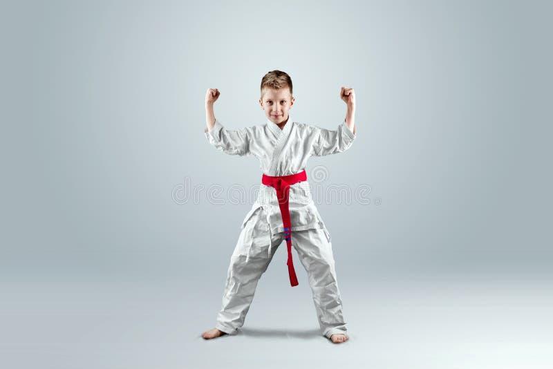 Creatieve achtergrond een kind in een witte kimono in een het vechten houding, op een lichte achtergrond het concept vechtsporten stock foto's