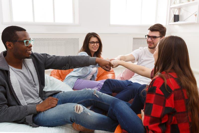 Creatieve bedrijfsteam gezette handen samen in het coworking van bureau stock foto