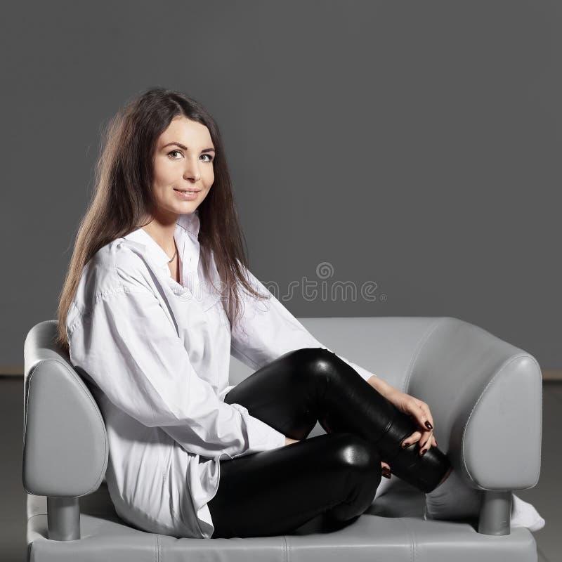 Creatieve bedrijfsvrouwenzitting op bureaustoel Geïsoleerd op grijze achtergrond stock foto's