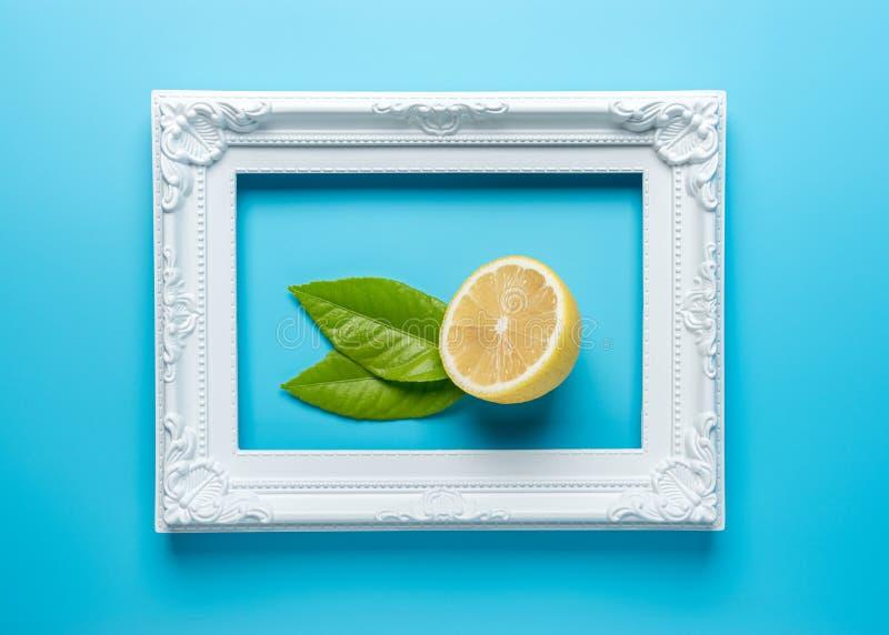 Creatieve de zomersamenstelling met gesneden citroen en wit kader op blauwe achtergrond Minimaal Voedselconcept stock foto