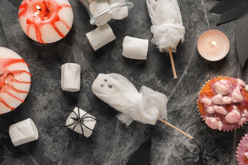 Creatieve desserts met heemst en cupcakes voorbereidingen getroffen voor Halloween-partij op grijze achtergrond stock foto's