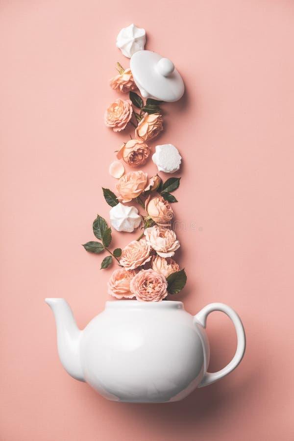 Creatieve die lay-out van de pot van de whtethee met oranje rozen en merengues op roze achtergrond wordt gemaakt royalty-vrije stock foto's