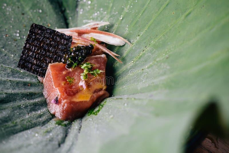 Creatieve Fijne Dinning: Sluit omhoog Tonijn met yuzu-miso bovenste laagje met zwarte die kaviaar en avocado in lotusbloemblad wo royalty-vrije stock foto