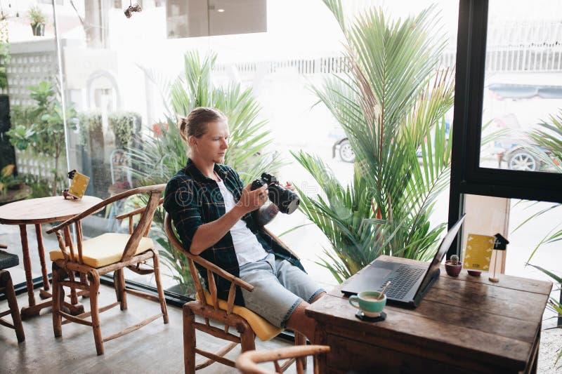 Creatieve fotograaf die professionele camera houden, die bij koffie met laptop zitten stock foto's