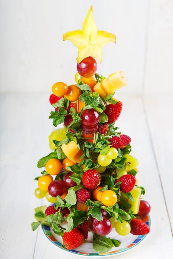 Creatieve fruitkerstboom met verschillende bessen, vruchten en stock foto's