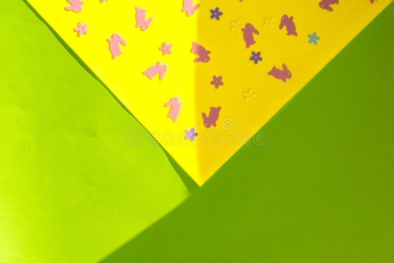 Creatieve Gelukkige Pasen - roze konijnen, konijntjes, bloemen op geel en Groenboek kleurrijke moderne geometrische achtergrond i royalty-vrije stock afbeelding