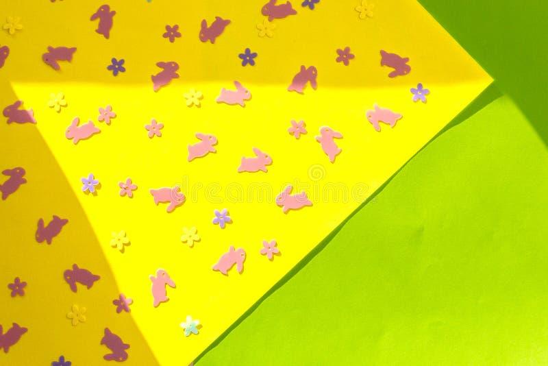 Creatieve Gelukkige Pasen - roze konijnen, konijntjes, bloemen op geel en Groenboek kleurrijke moderne geometrische achtergrond i stock foto