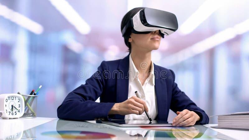 Creatieve grafische ontwerper die in vrbeschermende brillen tablet in bureau, modern apparaat trekken royalty-vrije stock afbeeldingen