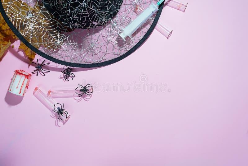 Creatieve Halloween-conceptenfoto van heksenhoed, spinnen en spuiten met diepe schaduwen op zachte roze achtergrond royalty-vrije stock afbeeldingen