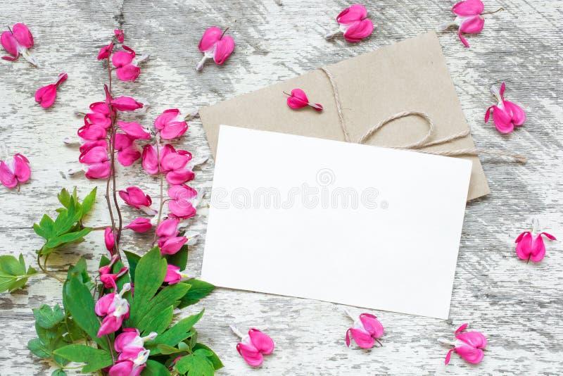 Creatieve het brandmerken spot tot vertoning uw kunstwerken lege groetkaart met roze bloemen met hart gevormde knoppen royalty-vrije stock afbeelding