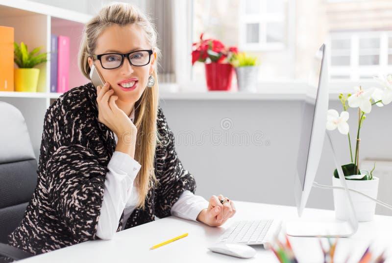 Creatieve jonge bedrijfsvrouw die op telefoon in bureau spreken royalty-vrije stock afbeelding