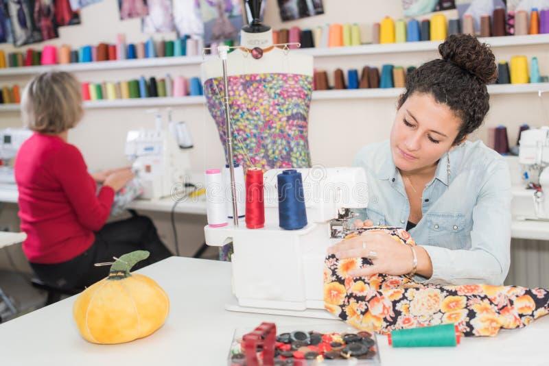 Creatieve jonge naaister die naaimachine met behulp van royalty-vrije stock foto