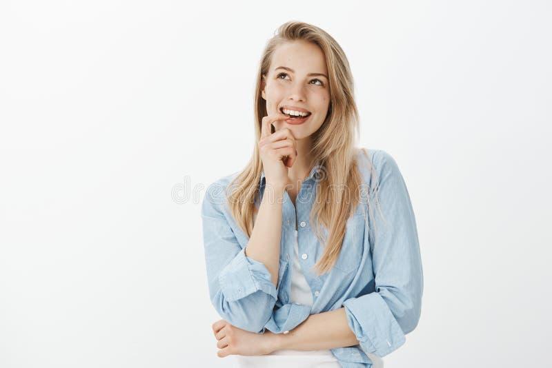 Creatieve knappe vrouwelijke ontwerper met blond haar, het bijten vinger, het kijken omhooggaand en het glimlachen merkwaardig te royalty-vrije stock afbeelding