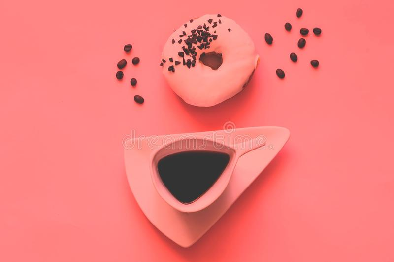 Creatieve kop van koffie en witte verglaasde doughnut met zwarte chocoladesnoepjes op koraalachtergrond Kleur van het jaar 2019 c stock fotografie