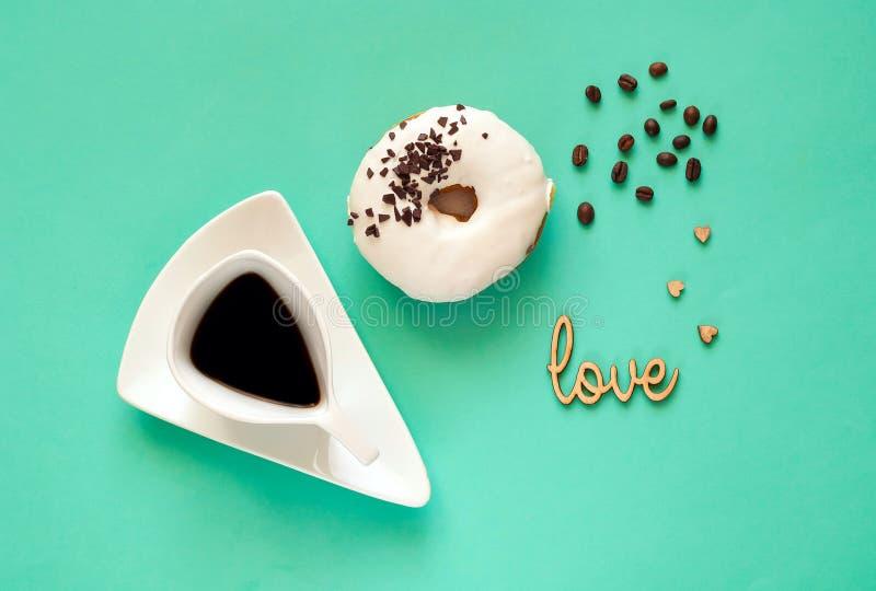 Creatieve kop van koffie en witte verglaasde doughnut met zwarte chocoladesnoepjes op muntachtergrond Voedselconcept, kleurrijk o stock fotografie