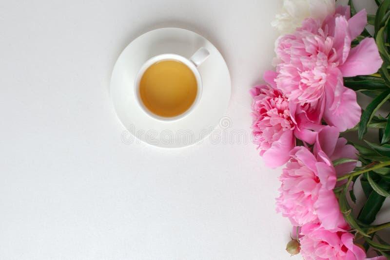 Creatieve lay-out met roze witte pioenenbloemen en kop thee op heldere lijst De lente Seizoengebonden valentijnskaart, vrouw, moe stock foto