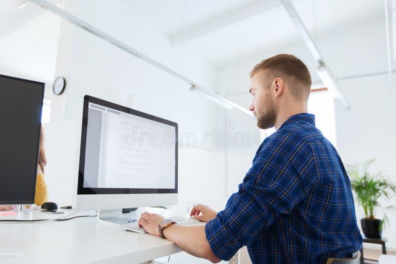 Creatieve mens of programmeur met computer op kantoor stock afbeeldingen