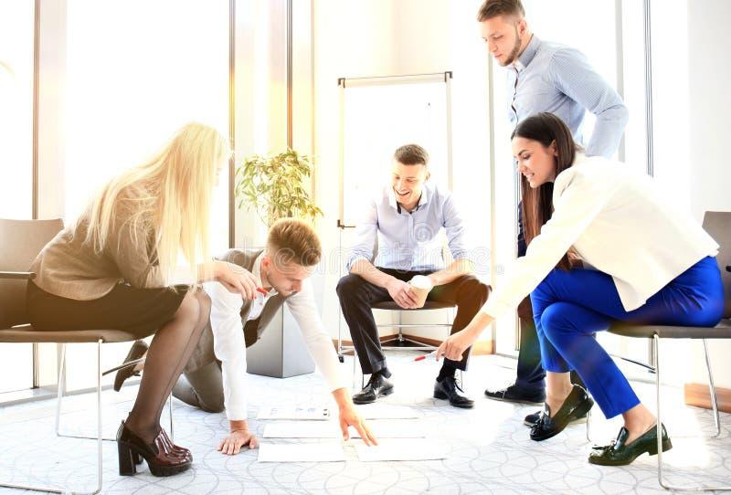 Creatieve mensen die projectplan bekijken die op vloer wordt opgemaakt Partners die projectplan in modern bureau bespreken stock afbeeldingen