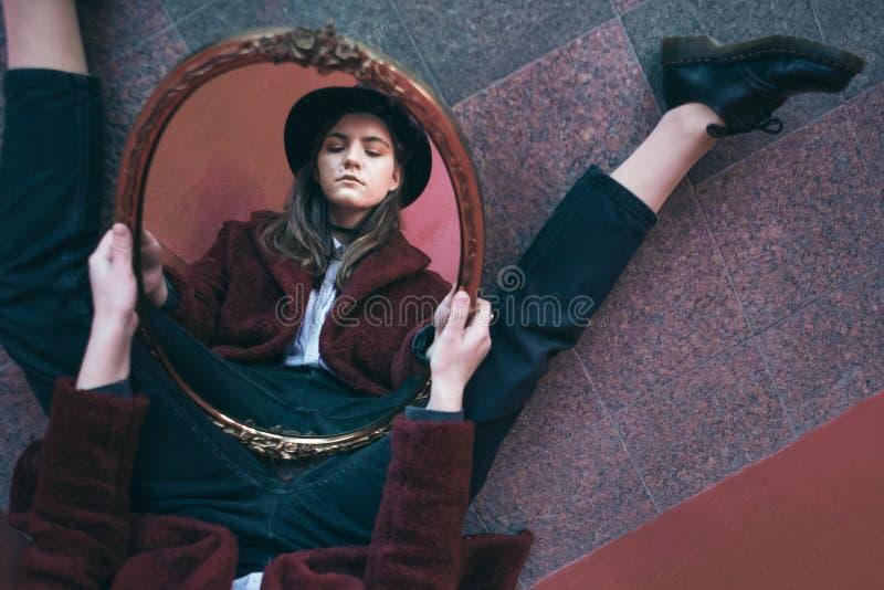 Creatieve Mooie het portretbezinning van het tienermeisje in de spiegel Rode kleuren artistieke stemming Tussen Droom en Werkelij royalty-vrije stock fotografie
