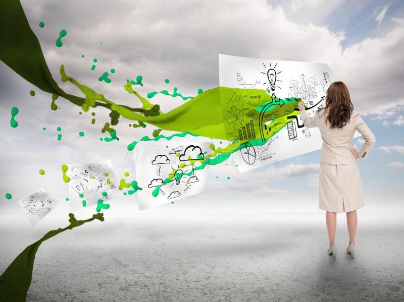 Creatieve onderneemster die op een document naast verfplons trekken stock foto's