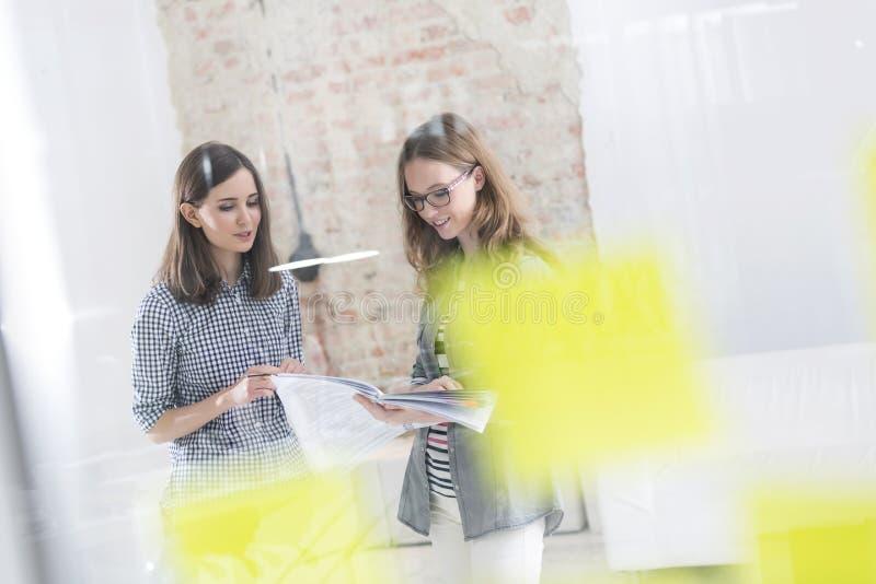 Creatieve onderneemsters die over documenten in bureau bespreken stock fotografie