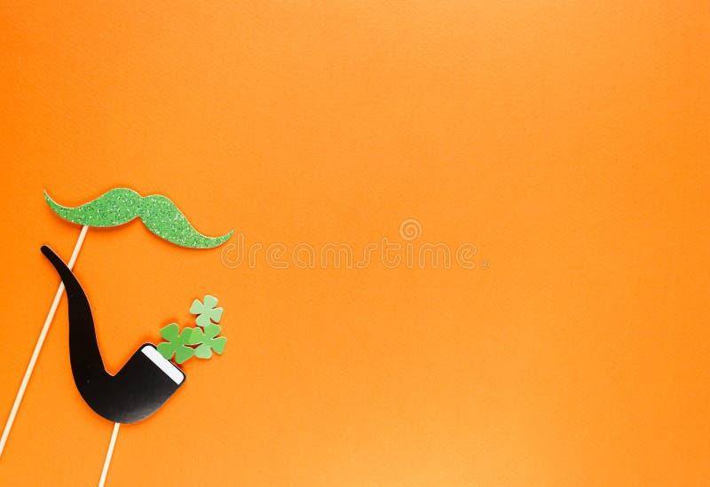 Creatieve st Patricks Dag oranje achtergrond Vlak leg samenstelling van Ierse vakantieviering met het decor van de fotocabine: ho royalty-vrije stock fotografie