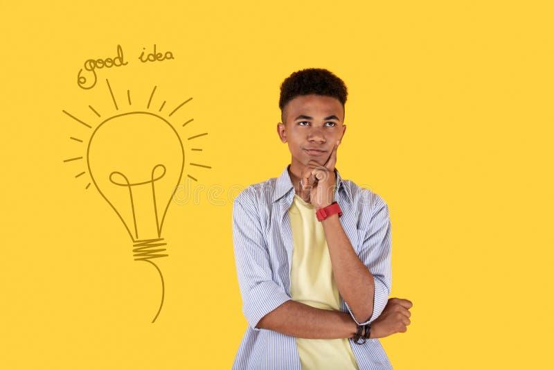 Creatieve student zorgvuldig wat betreft zijn gezicht terwijl het krijgen van een idee royalty-vrije stock afbeeldingen