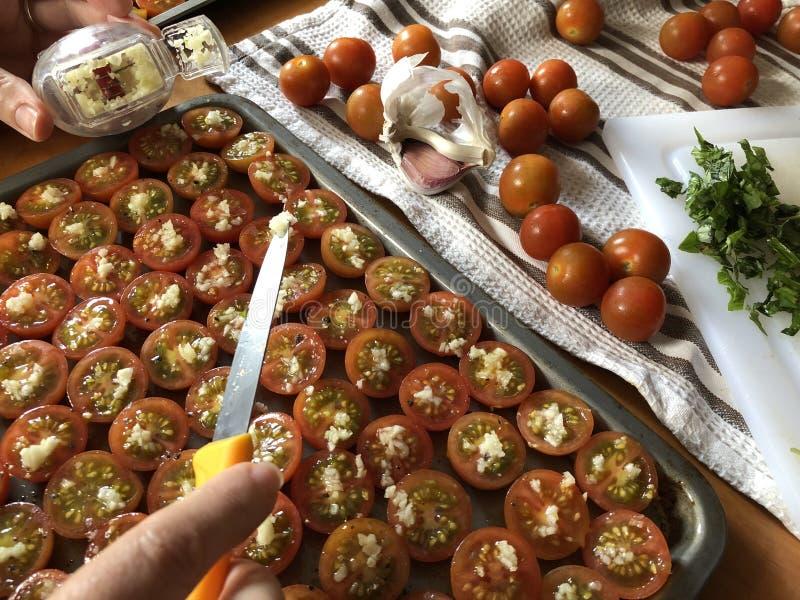 Creatieve voedselfotografie Vrouw die tomaten voor het roosteren voorbereiden stock afbeelding