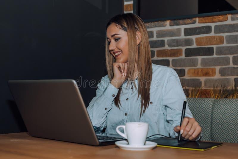 Creatieve vrouw die aan laptop werken terwijl het gebruiken van grafische tablet in koffie royalty-vrije stock fotografie