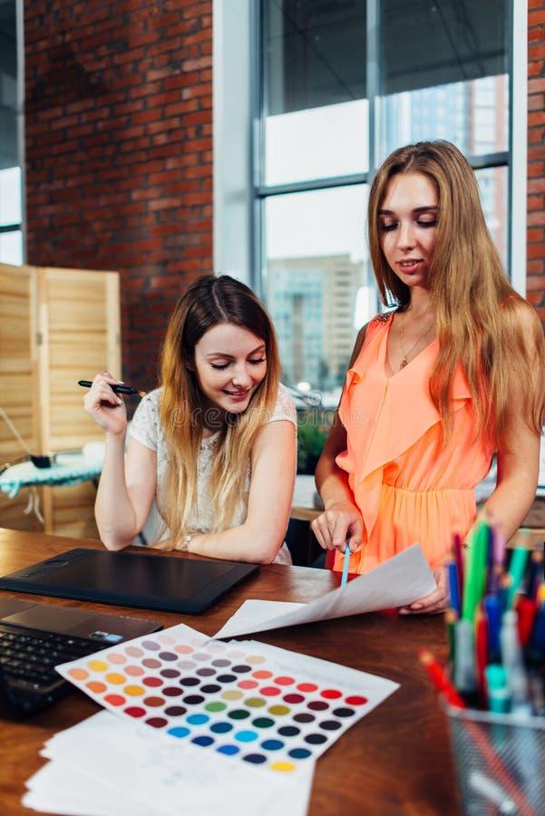 Creatieve vrouwelijke binnenhuisarchitect die met een klant die in haar bureau werken kleuren voor een nieuw ontwerp kiezen die k stock foto