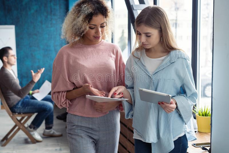 Creatieve vrouwelijke ontwerpers die in team werken Twee Onderneemsters die Informele Vergadering in Modern Bureau hebben royalty-vrije stock afbeelding