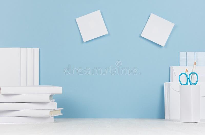 Creatieve werkplaats voor ontwerpers en studenten - witte bureaukantoorbehoeften, lege stickers op lijst en blauwe achtergrond royalty-vrije stock afbeelding