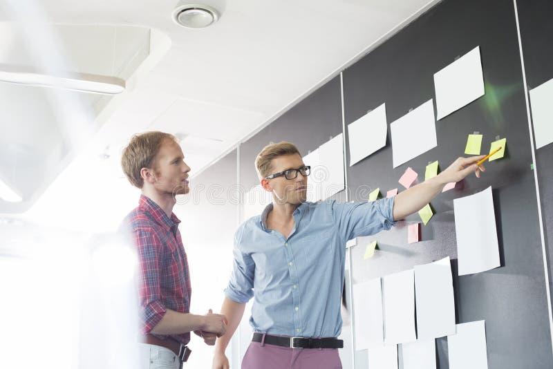 Creatieve zakenlieden die over kleverig document op muur in bureau bespreken royalty-vrije stock afbeelding