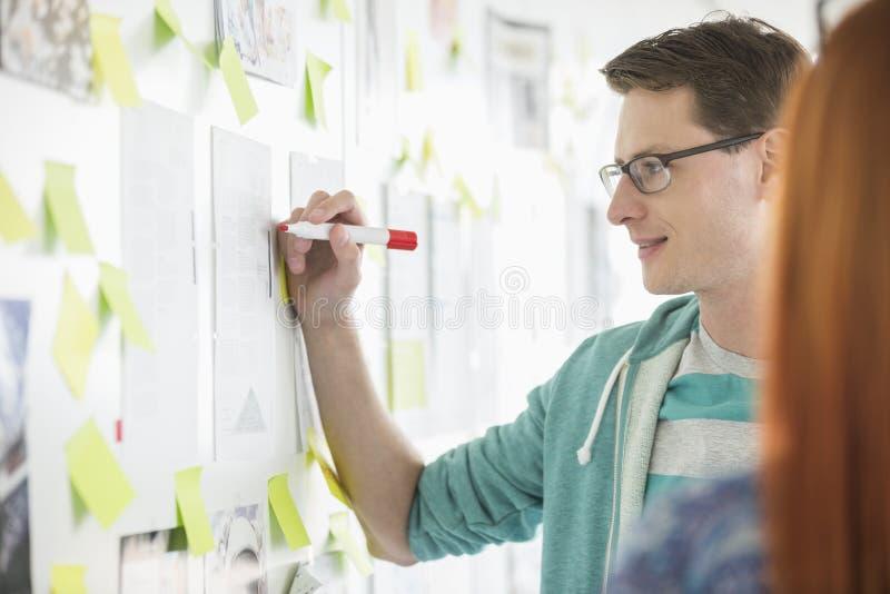 Creatieve zakenman het schrijven nota's op papier in bureau royalty-vrije stock afbeeldingen