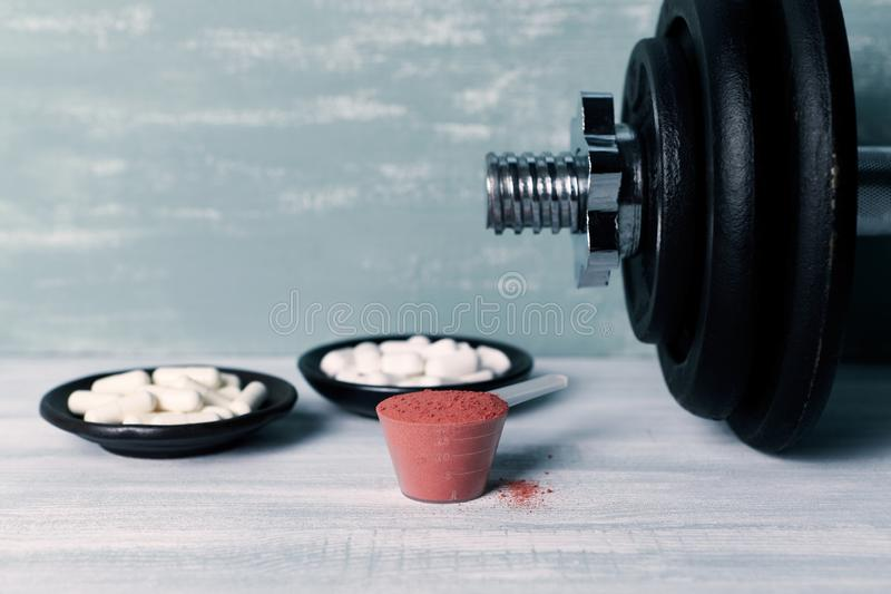 Creatine Powder, Aginine capsules, BCAA amino acids and a dumbbell in background. Sport nutrition. Wooden background. Close up stock images