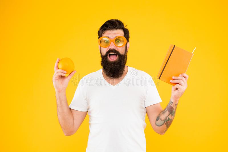 Creating a balanced reading diet. Hipster holding orange fruit and book for reading on yellow background. Bearded man in stock photography