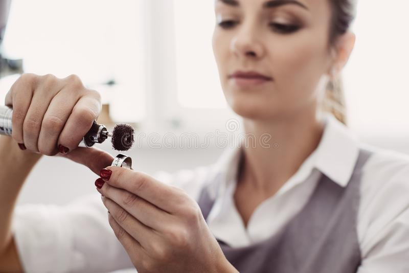 Creating a beauty. Close-up portrait of young female jeweler preparing polishing tool for making jewelry. royalty free stock photos