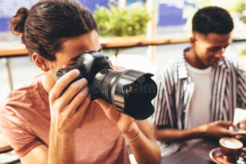 Creating content for social media. Man taking pictures for channel while sitting at cafe with friends. Friends meeting at cafe taking pictures royalty free stock image
