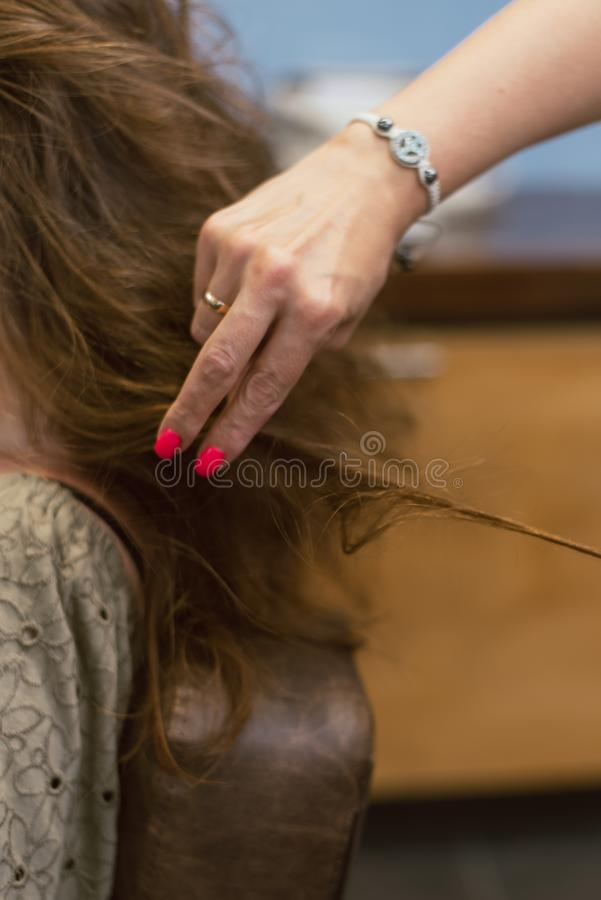 Creating hairstyles on brown brown hair in the salon. Creating curls at the hairdresser royalty free stock images