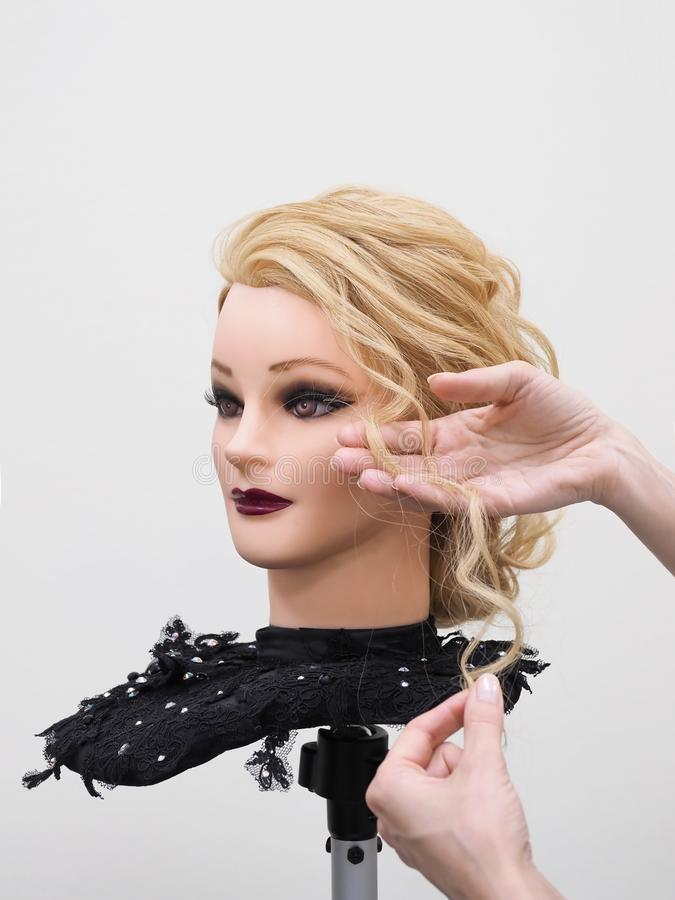 Creating hairstyles on a mannequin. Training hair styling on a mannequin royalty free stock photos