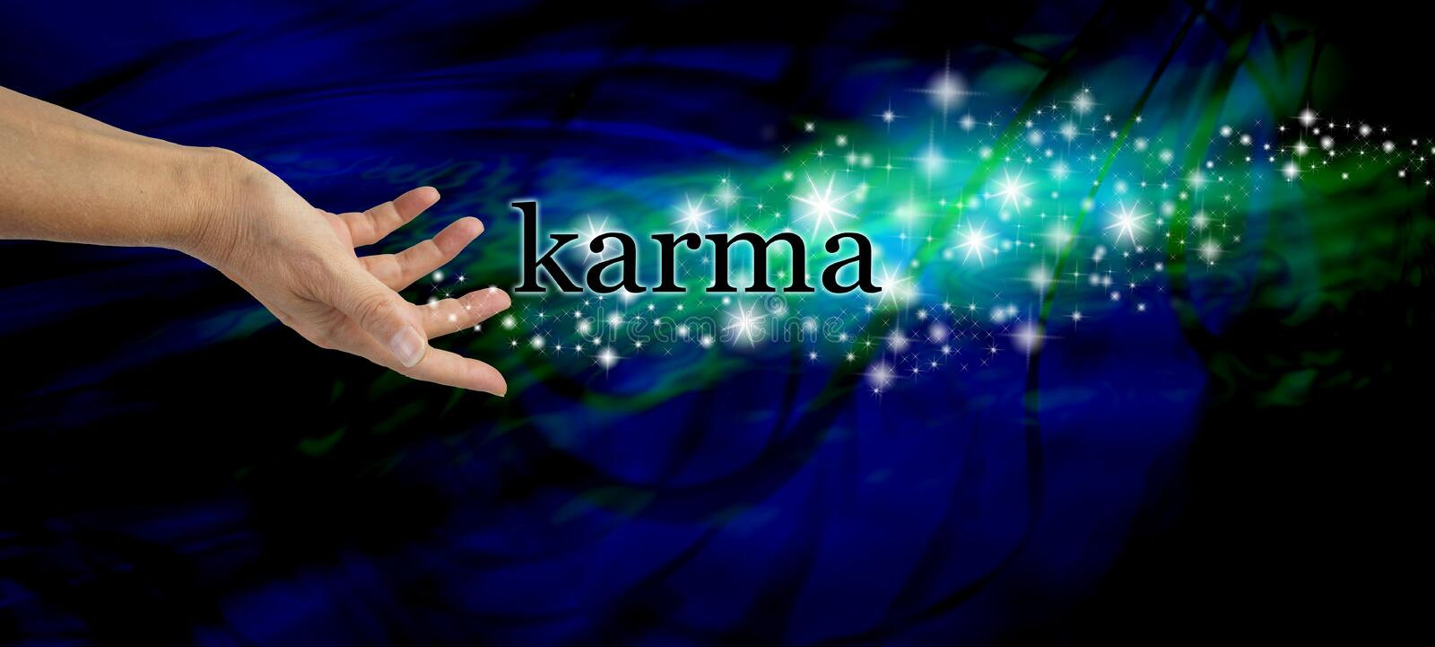 Creating Karma. Female hand outstretched with the word 'Karma' floating away amongst a stream of sparkles on a dark blue swirling background with a swirl of stock images
