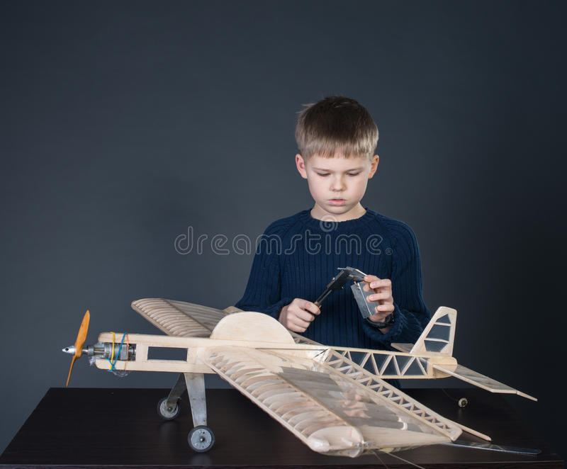 Creating the model plane. Measuring thickness. Plane modeling hobby. Little boy with wooden airplane model royalty free stock images
