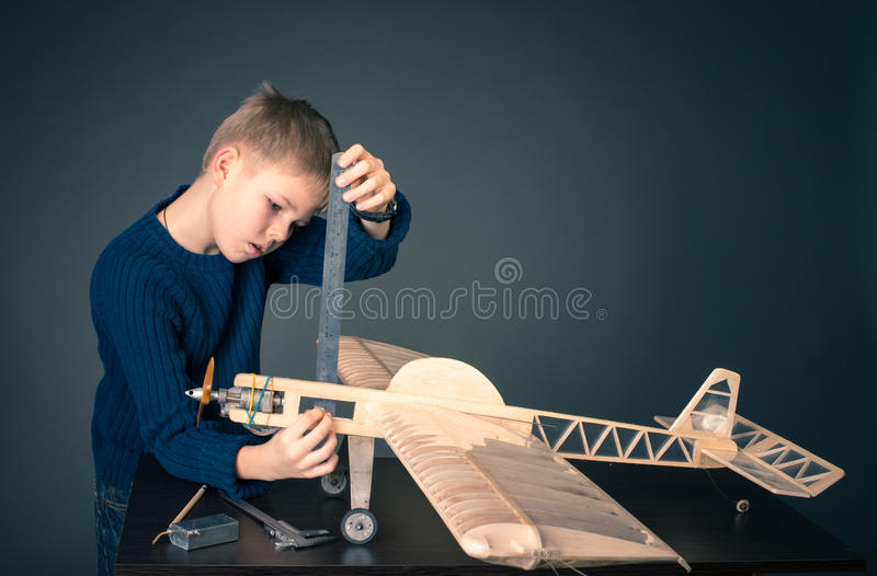Creating the model plane. Measuring thickness. Plane modeling. Little boy with wooden airplane model royalty free stock photography