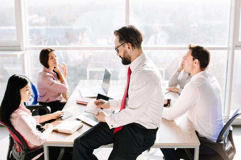 Creating of new important project. Two male and two female managers in office sitting at desk. Ctreating project plan royalty free stock photography
