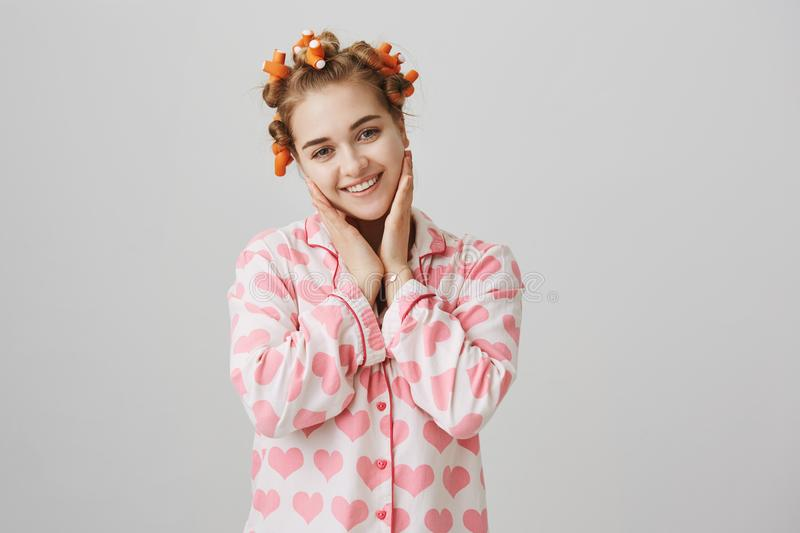 Creating perfect hairstyle. Adorable slender european girl in hair curlers and pyjamas with heart template. standing stock image